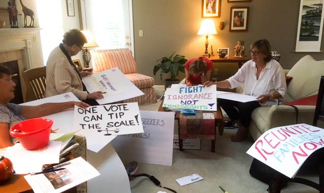 Members of the group, Defending Democracy create signs for rally